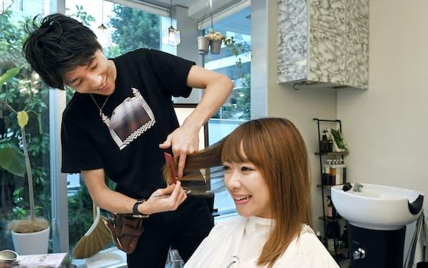女性客の髪をカットする山内さん(東京都渋谷区ヘアサロンの「i.」)