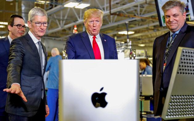米テキサス州オースティンの工場で、トランプ米大統領(中央)にアップルの生産拠点を説明するクック最高経営責任者(CEO、左)=ロイター