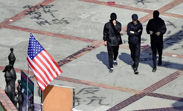 香港理工大構内を歩くデモ隊のメンバーら。米国旗が掲げられていた=20日、香港(共同)