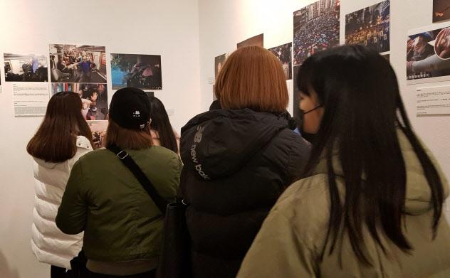15日に若者の街、弘大で開かれた香港デモの展示会。生々しい現場の様子に多くの若者が見入っていた