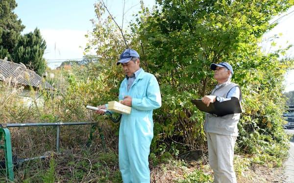 赤宇木で線量を定点測量する今野邦彦さん(左)と今野義人さん(福島県浪江町)
