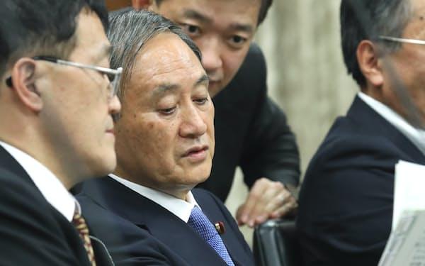 参院内閣委で資料に目を通す菅官房長官(21日)