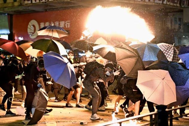 香港理工大の周辺で火の粉から逃げるデモ隊=18日、香港(共同)
