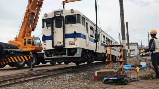 脱線した列車をクレーン車でつり上げる訓練も(22日、北九州市)