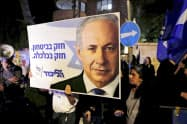 21日、エルサレムで、イスラエル検察の起訴に抗議し、ネタニヤフ首相の自宅周辺に集まった支持者ら=ロイター
