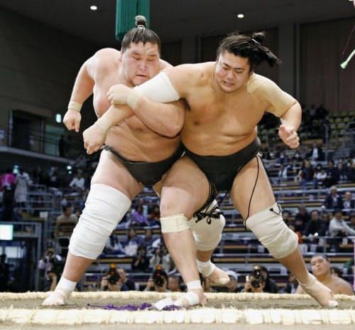 対馬洋(右)を攻める照ノ富士(22日、福岡国際センター)=共同