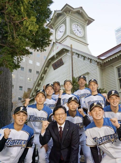 時計台の前でポーズを取る日本ハムの栗山監督(前列中央)とドラフト1位の河野竜生投手(同左)ら新入団選手(23日、札幌市)=共同