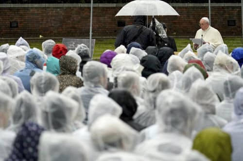 雨のなか、ローマ教皇フランシスコのスピーチを聞く参加者(24日長崎市の爆心地公園)=AP