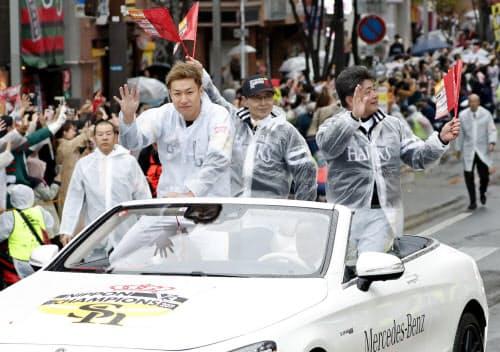 プロ野球で3年連続日本一を達成し、福岡市内で行われた祝賀パレードでファンの声援に応えるソフトバンクの(左から)柳田選手会長、王球団会長、工藤監督(24日)=共同