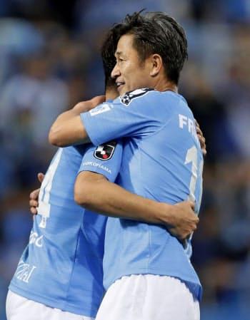 愛媛に快勝しJ1昇格を決め、チームメートと抱き合って喜ぶ横浜FC・三浦=右(24日、ニッパツ球技場)=共同