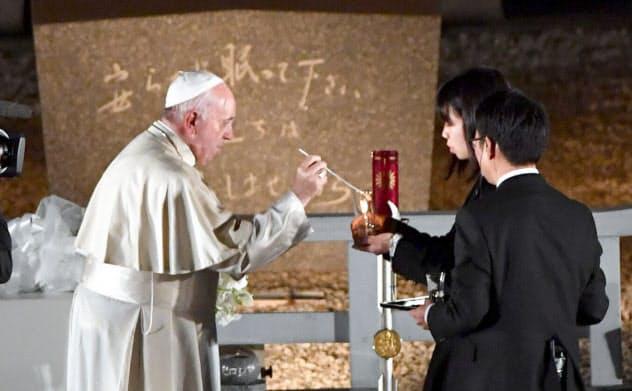 高校生平和大使から明かりをとるローマ教皇フランシスコ(左)(24日夜、広島市中区の平和記念公園)=代表撮影