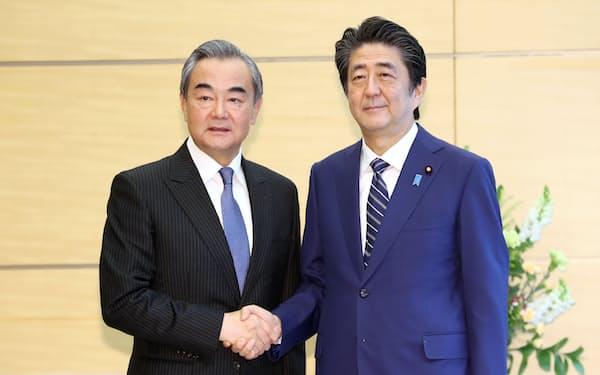 会談を前に中国の王毅外相(左)と握手する安倍首相(25日午前、首相官邸)