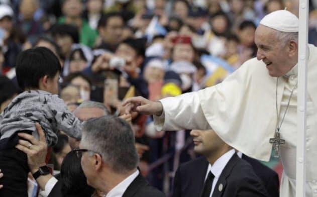 11月24日、長崎でミサの前に子供と手を触れあうフランシスコ教皇=AP