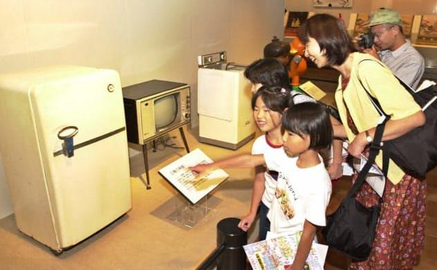 昭和30年代の「三種の神器」を見る親子連れら(東京・墨田区の江戸東京博物館)