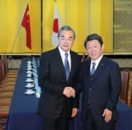 会談を前に握手する茂木外相(右)と中国の王毅外相(25日、東京都港区)=代表撮影