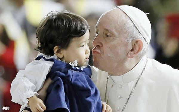 東京ドームで行われた大規模ミサで、子どもにキスをするローマ教皇フランシスコ=25日午後、東京都文京区