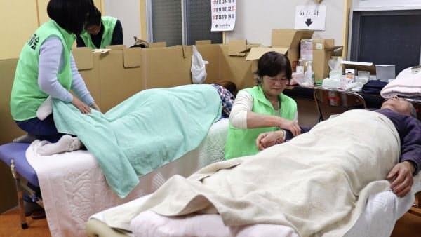 福島県郡山市の避難所でマッサージのボランティア活動をする鍼灸師(13日)=共同