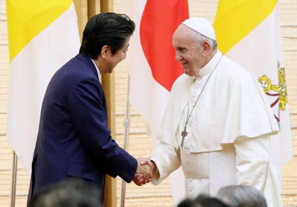 首相官邸で開かれた要人らとの集いでスピーチを終え、安倍首相と握手するローマ教皇フランシスコ(25日)