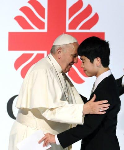 東日本大震災の被災者(右)と抱擁を交わすローマ教皇フランシスコ(25日、東京都千代田区)