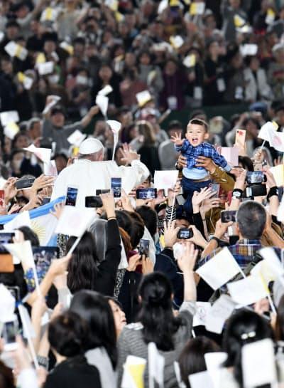 ミサの会場に入るローマ教皇フランシスコに手をふる子ども(25日、東京都文京区の東京ドーム)