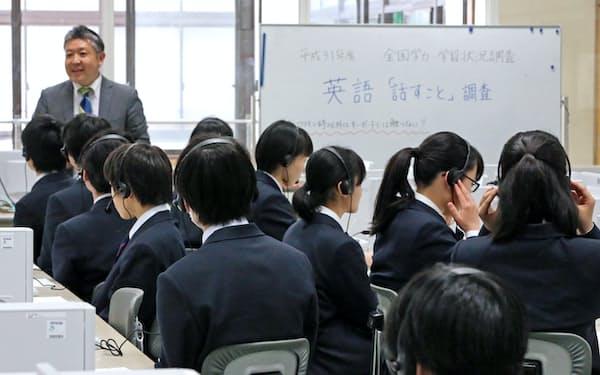 ヘッドセットを着けて全国学力テストの英語「話す」の試験に臨む中学3年生(18日、都内)