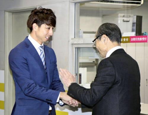 ソフトバンクの球団事務所を訪れ、王球団会長(右)と握手する福田秀平外野手(26日、ヤフオクドーム)=共同