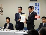 岸田政調会長は西村経財相に経済対策に関する要望書を手交した。(26日、自民党本部)