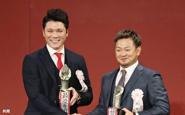 MVPを受賞し、笑顔で握手を交わす巨人・坂本勇(左)と西武・森(26日、東京都内のホテル)=共同