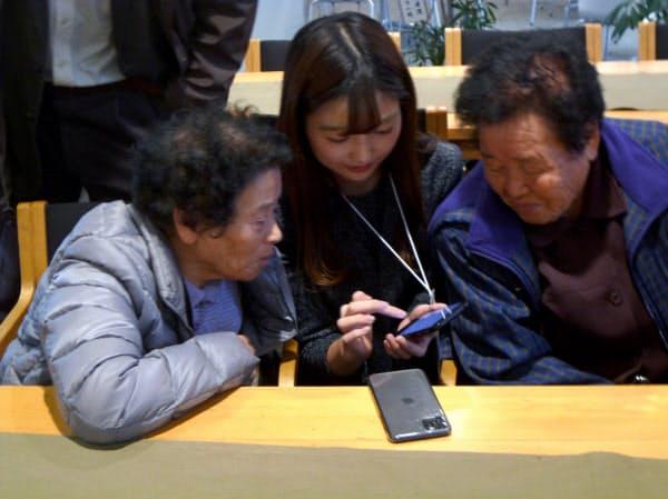 アジットの社員(中)が山古志地区の住民にアプリの使い方を説明した(11月20日)