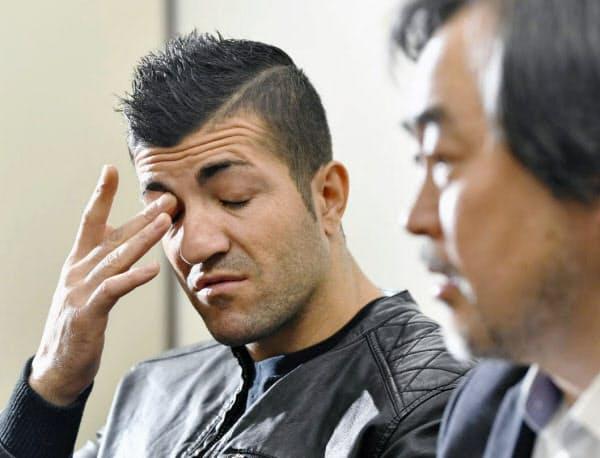 司法記者クラブで記者会見するクルド人男性(左)(26日午後、東京・霞が関)=共同