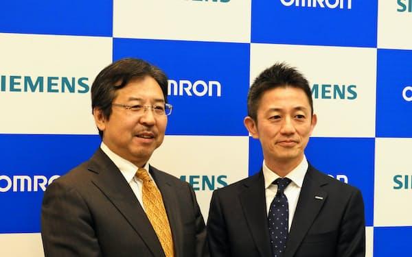 オムロンはシーメンスのクラウド基盤を活用し、複数の工場の製造データを連係させる(オムロン執行役員の山本真之氏(右)とシーメンス日本法人社長の藤田研一氏)