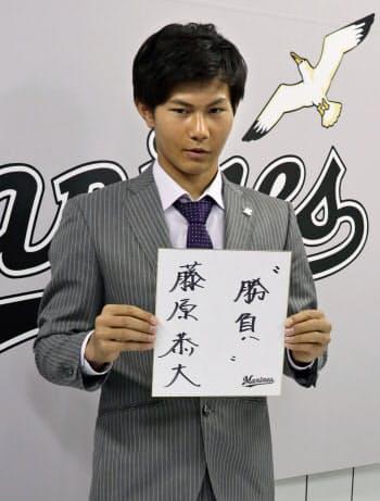 契約更改を終え、記者会見で色紙を手に写真撮影に応じるロッテの藤原恭大外野手(27日、千葉市のZOZOマリンスタジアム)=共同