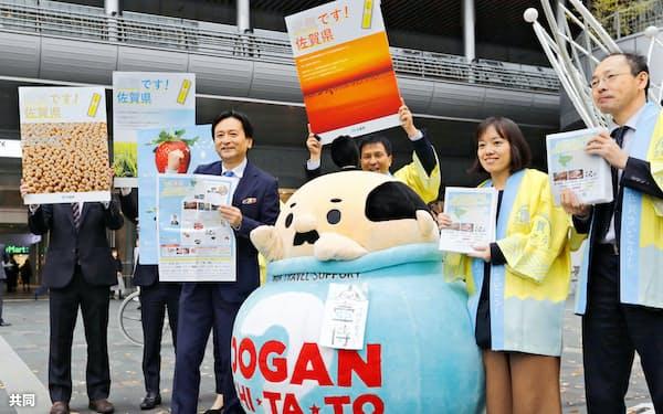 佐賀県内の観光地や県産品をPRする新聞を手にする佐賀県の山口祥義知事(左)ら(27日午前、JR博多駅前)=共同