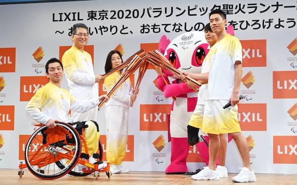 トーチを手に記念写真に納まるテニスの錦織選手(右)ら(27日、東京都江東区)