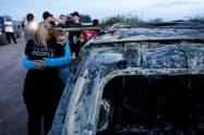 麻薬カルテルと見られる集団に襲われた車両のそばで抱き合う被害者の親族(メキシコ北部ソノラ州)=ロイター
