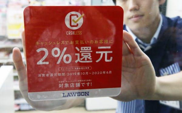 キャッシュレス決済で2%還元を知らせるステッカーを貼るコンビニの店員(10月1日、東京都内)
