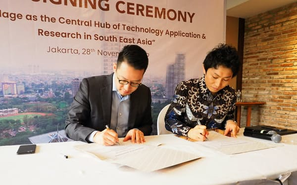 28日、ジャカルタで提携の覚書に署名するリッポー・カラワチのジョン・リアディ最高経営責任者(左)とソフトバンクの北原秀文グローバル事業戦略本部本部長