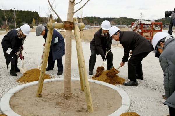 宮城県南三陸町の震災復興祈念公園で行われた桜の植樹式に参加した佐藤仁町長(左から4人目)ら=共同