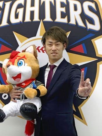 年俸1億円の大台に復帰し、「1」のポーズをとる日本ハムの秋吉亮投手(28日、札幌市)=共同