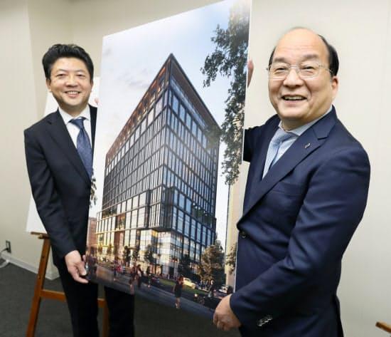 新しいビルのイメージ図を手にする西鉄の倉富社長(右)とイオンの吉田副社長(28日、福岡市)