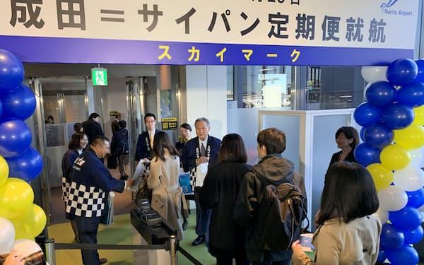 乗客に記念品を手渡して初の国際定期便を祝った(29日、成田空港)