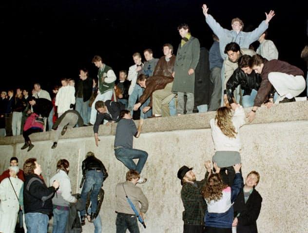 東独政府の国境開放後の1989年11月10日未明、東側からベルリンの壁をよじ登る市民たち(ロイター=共同)