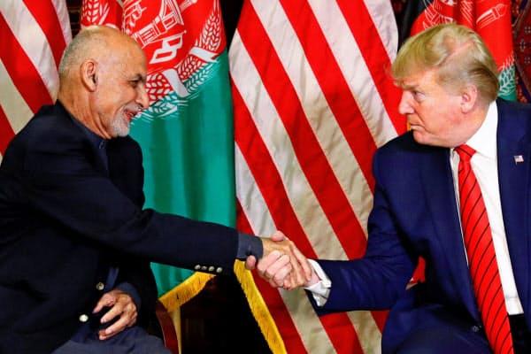28日、アフガニスタンのガニ大統領(左)と会談したトランプ米大統領(アフガニスタン東部)=ロイター