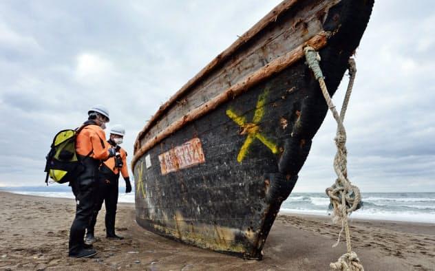 漂着した木造船の船番号を記録する青森機動監視隊の隊員(青森県つがる市)