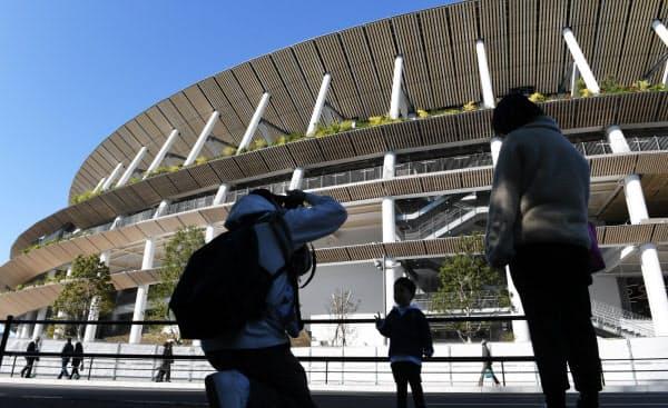 完成を迎えた新国立競技場の前で記念写真を撮る人たち(30日、東京都新宿区)