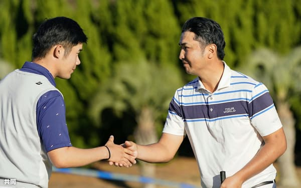 第3日、ホールアウトし、同組選手と握手を交わす小林伸太郎(右)。通算13アンダーで2位(30日、Kochi黒潮CC)=共同