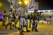1日、香港でデモの参加者を取り締まる警察官ら=AP・共同