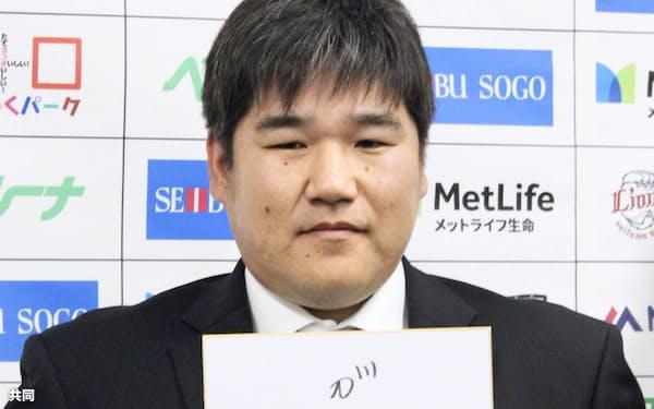 契約更改を終え、来季の意気込みを書いた色紙を手にする西武の中村(2日、埼玉県所沢市の球団事務所)=共同