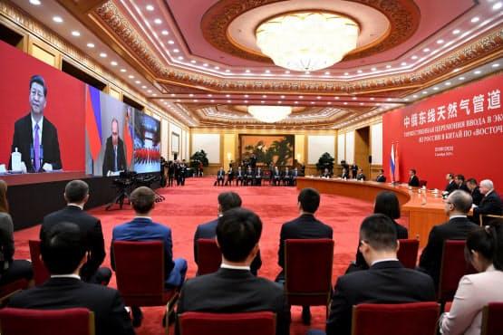 中国の習国家主席は2日の稼働式典で、テレビ中継で参加したロシアのプーチン大統領とあいさつを交わした=ロイター