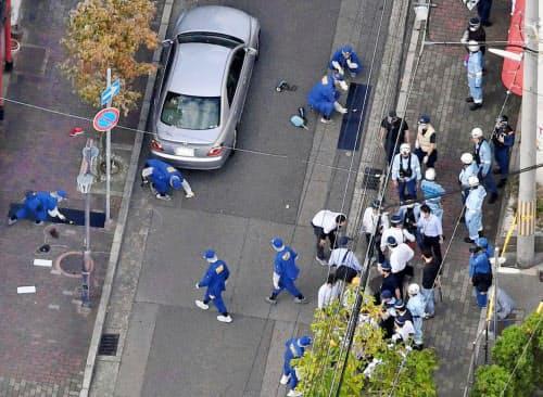 暴力団関係者の銃撃事件現場を調べる兵庫県警の捜査員ら(10月10日、神戸市)=共同